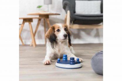 Het Trixie Push Away hondendenkspel heeft twee kegels en twee afdijkschijven met daaronder kommetjes om voertjes in te plaatsen. De uitdaging is dat de hond eerst de kegels verplaatst en daarna pas de schijfjes kan verplaatsen.